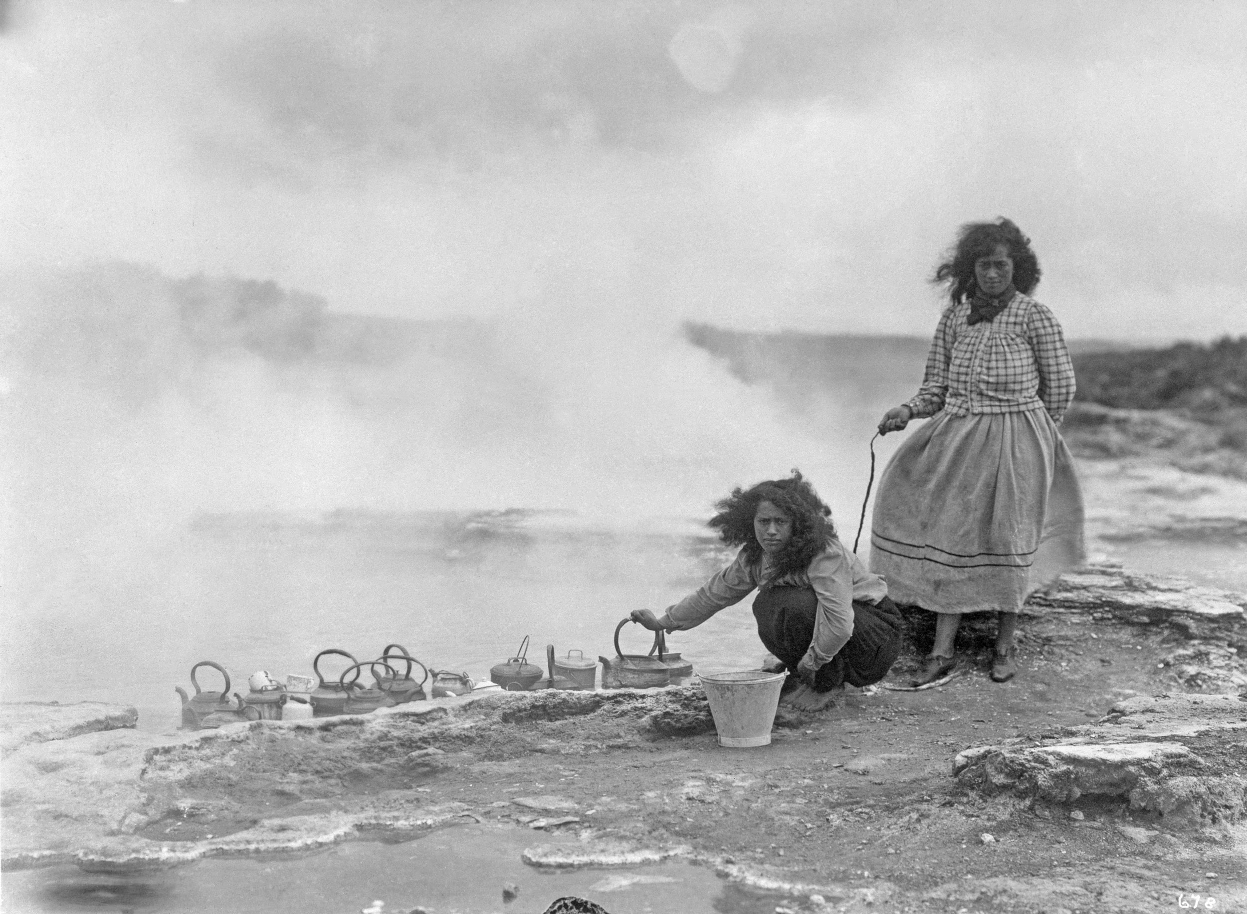 Maori women cooking food and boiling kettles in steam holes